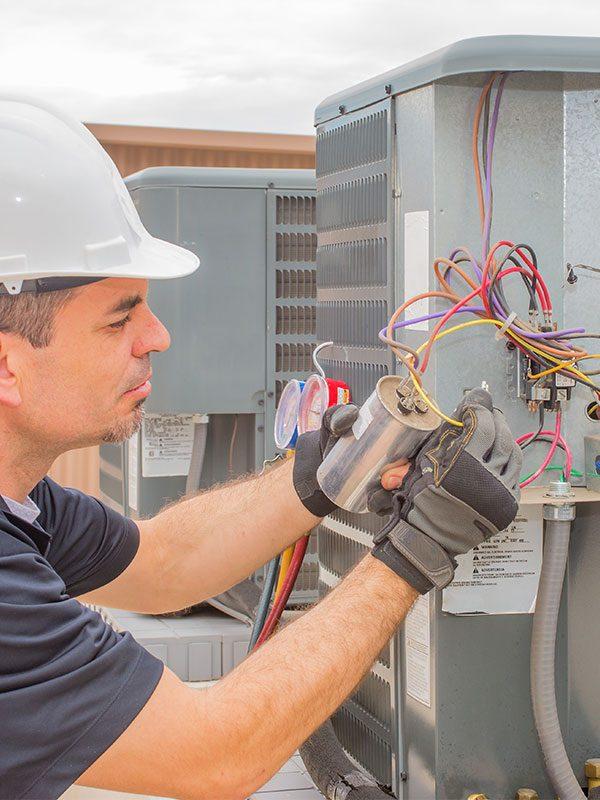 Hvac technician checking a run capacitor on a condenser